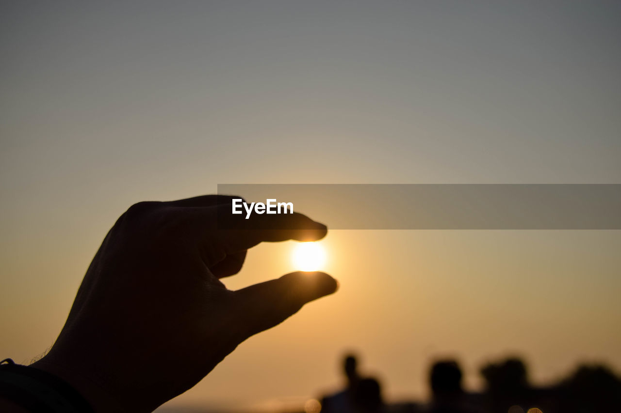 human hand, sky, sunset, hand, human body part, real people, sun, lifestyles, body part, holding, unrecognizable person, human finger, personal perspective, silhouette, finger, nature, orange color, leisure activity, one person, focus on foreground, outdoors