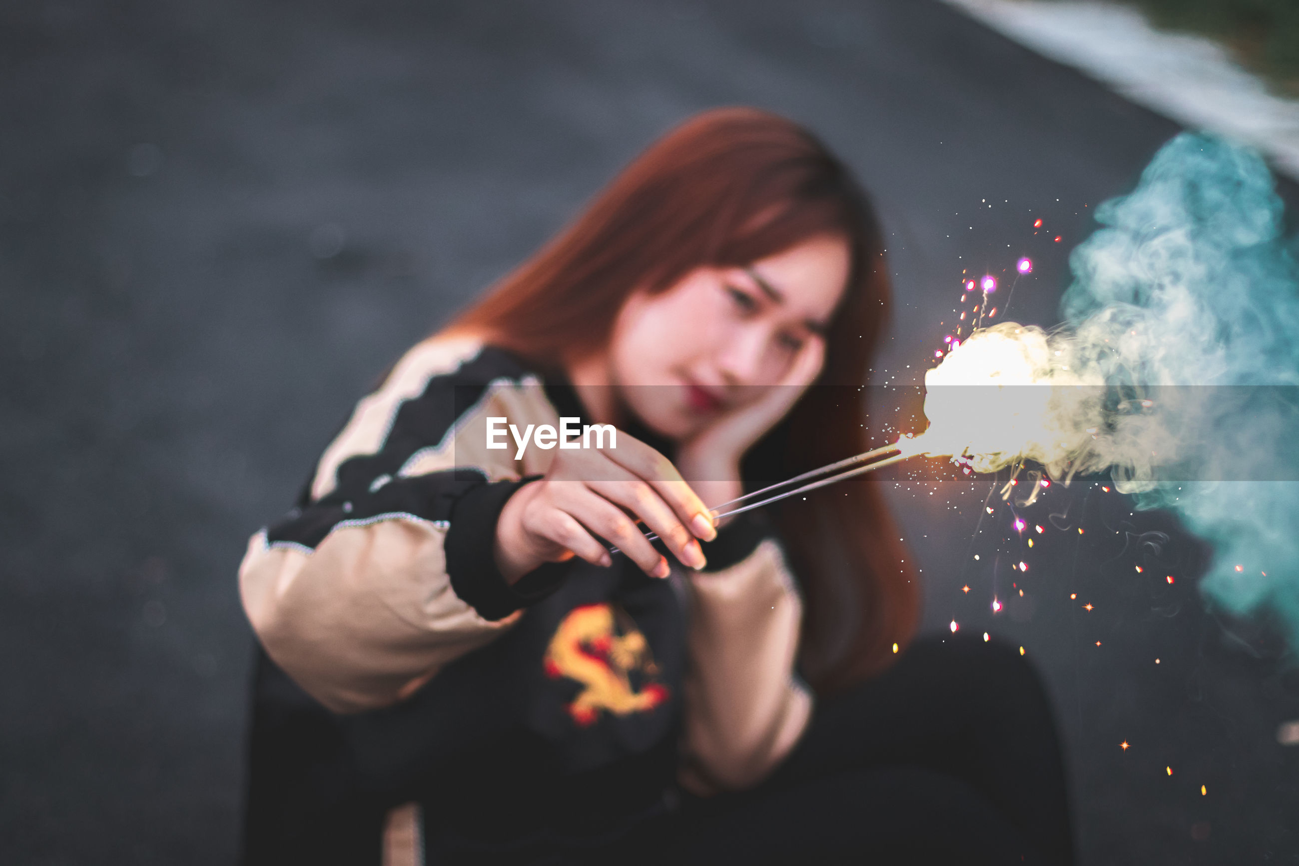 Young woman holding sparklers while sitting outdoors