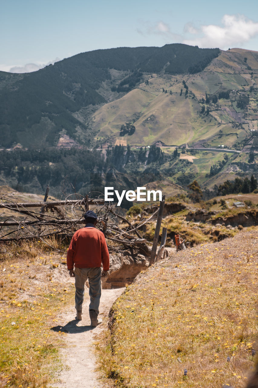 mountain, rear view, full length, scenics - nature, men, beauty in nature, one person, landscape, nature, environment, real people, mountain range, leisure activity, non-urban scene, lifestyles, day, tranquility, hiking, tranquil scene, outdoors, looking at view