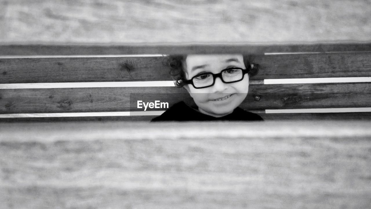 Boy in eyeglasses seen through wooden wall