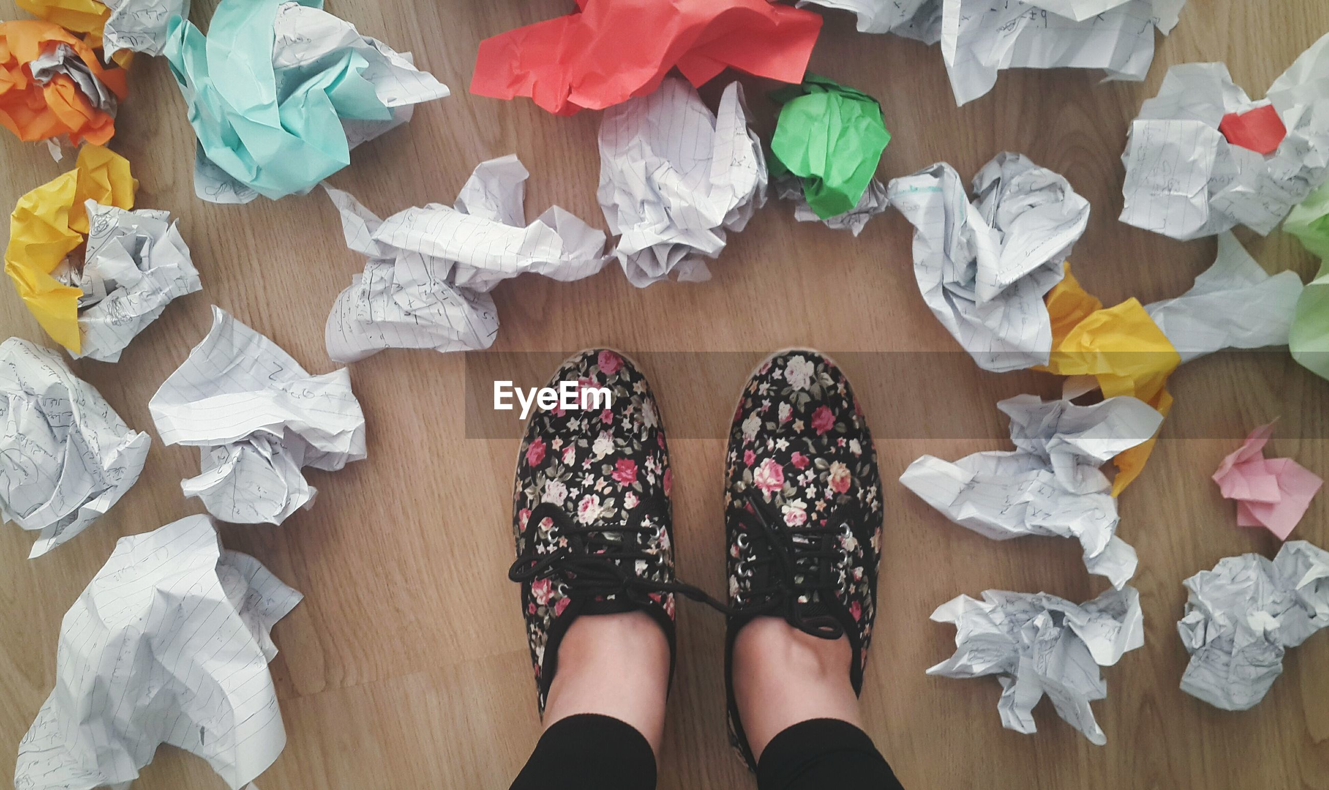 Low section of person standing amidst crumpled paper balls on floor
