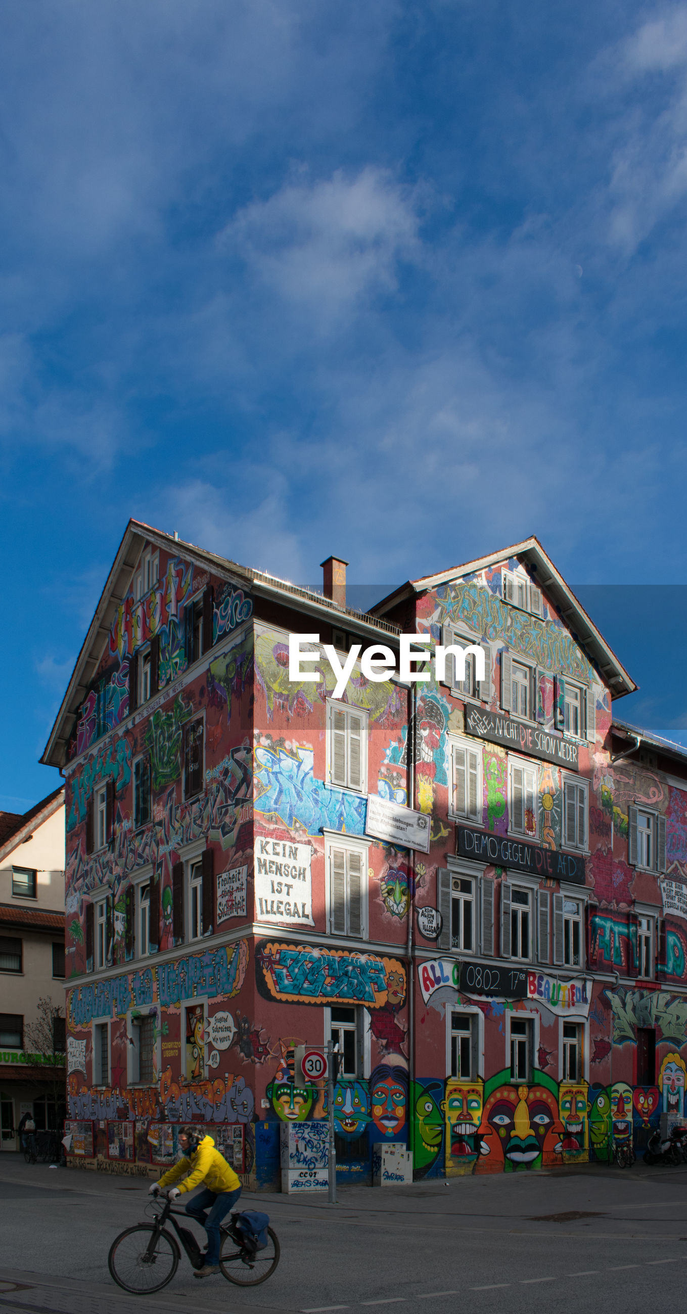 building exterior, architecture, built structure, transportation, city, sky, mode of transportation, cloud - sky, bicycle, land vehicle, one person, building, street, graffiti, real people, road, day, men, residential district, outdoors, riding, mural