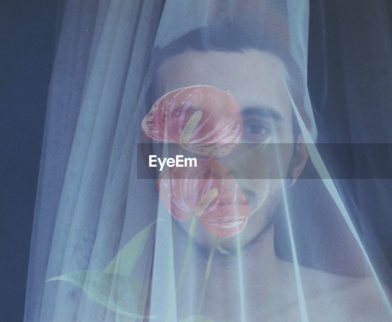 Close-up portrait of man against curtain