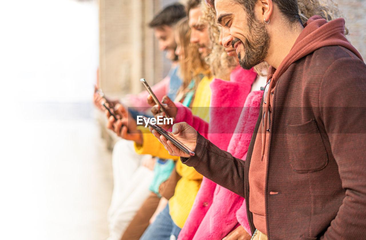 Friends using smart phones in city