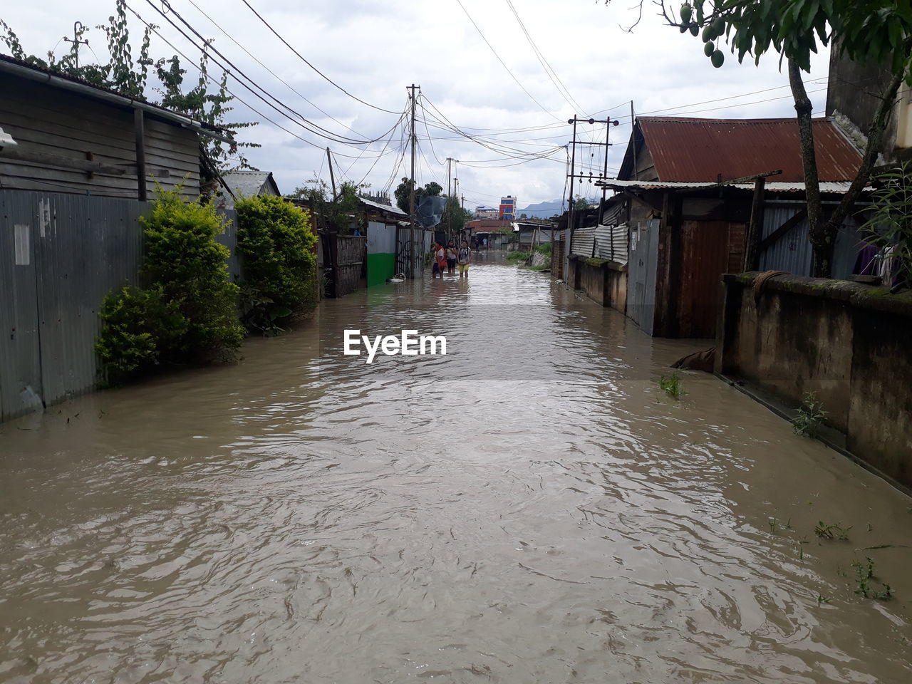 Women wading in flood by houses