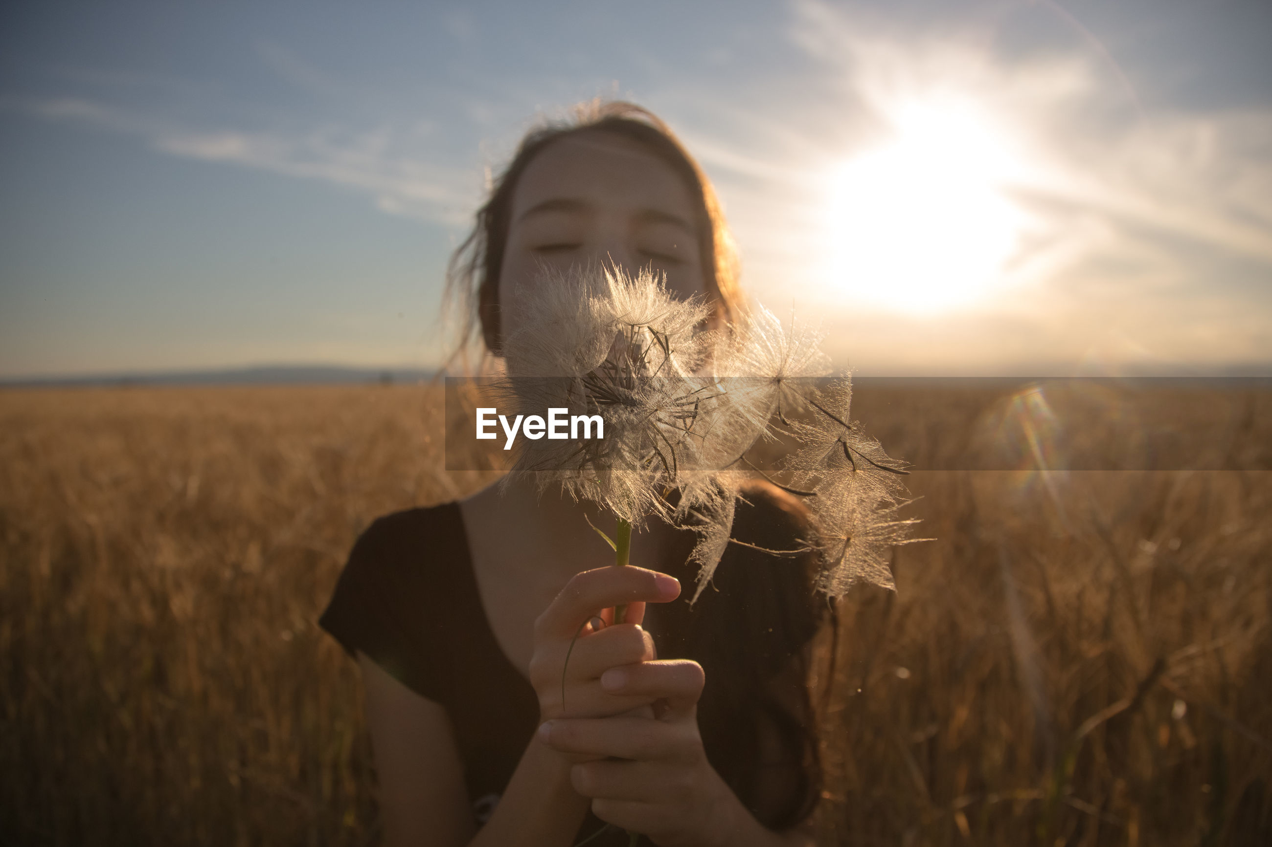 Young woman blowing dandelion on field against sky