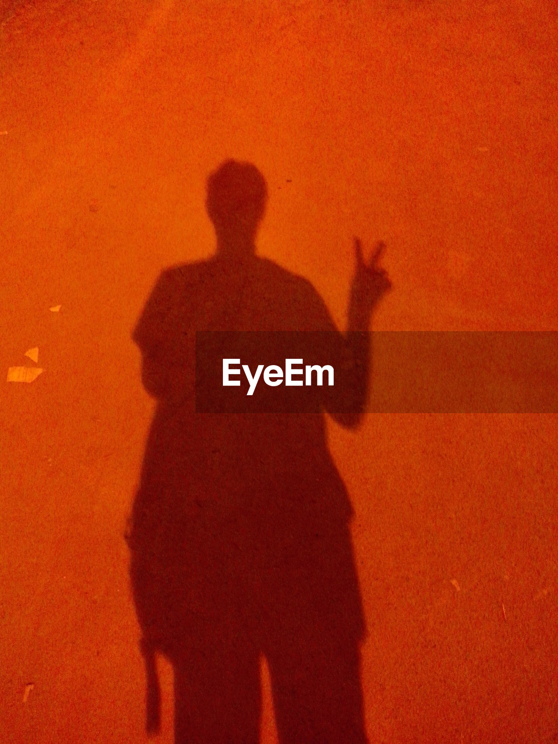 Man's shadow displaying victory sign