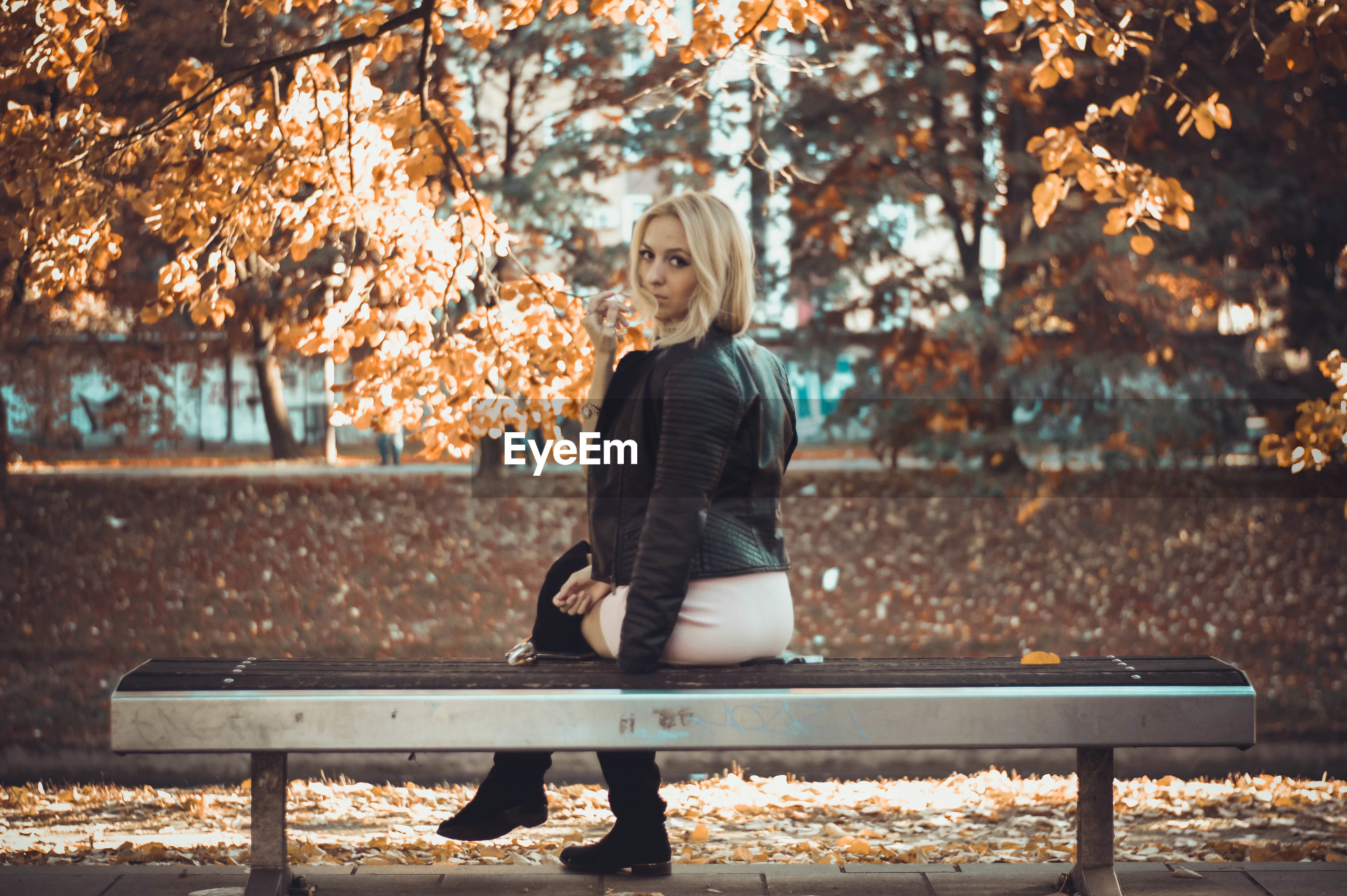Portrait of beautiful woman sitting on bench at park