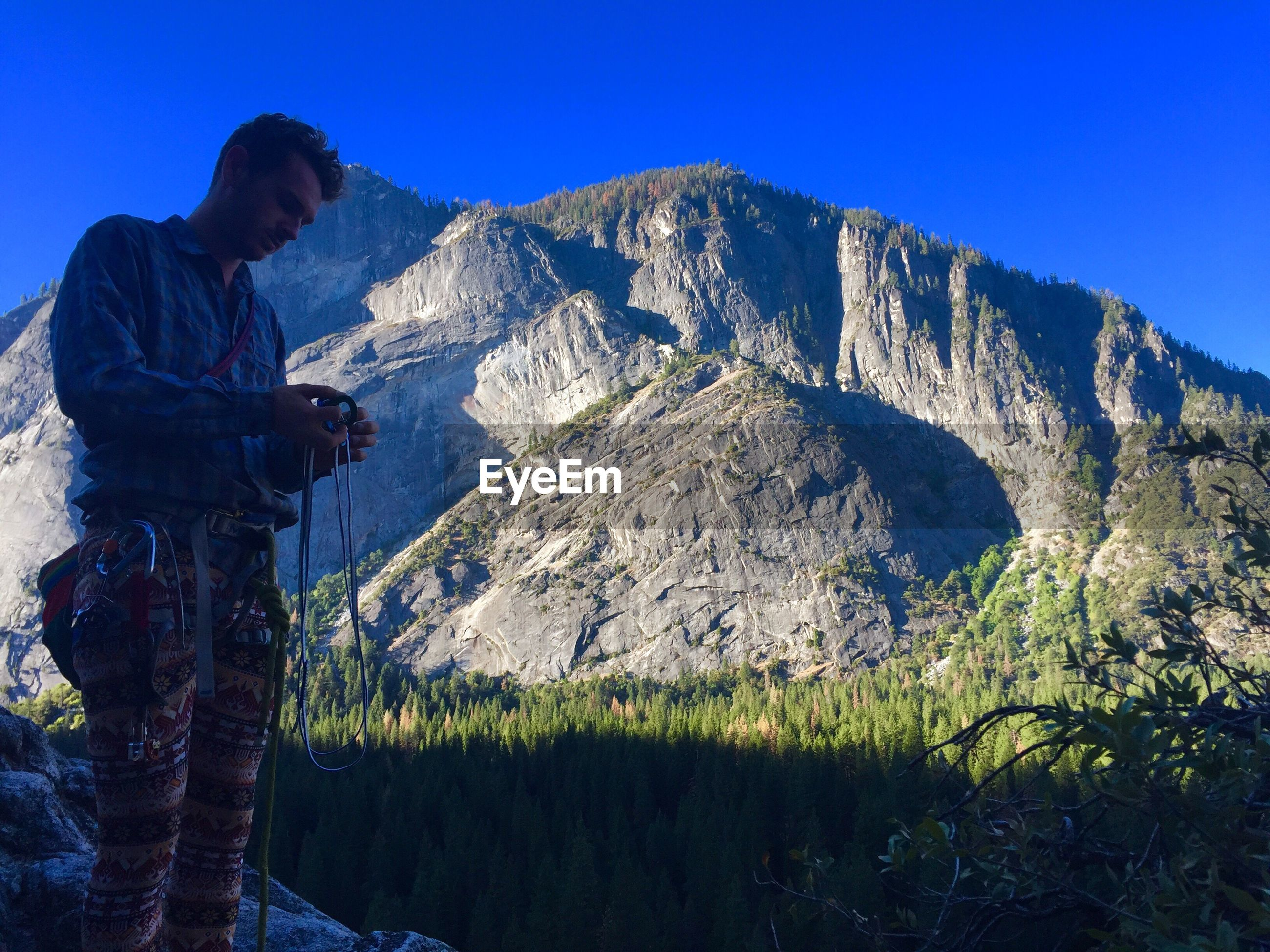 Man holding harness while standing against mountain at yosemite national park