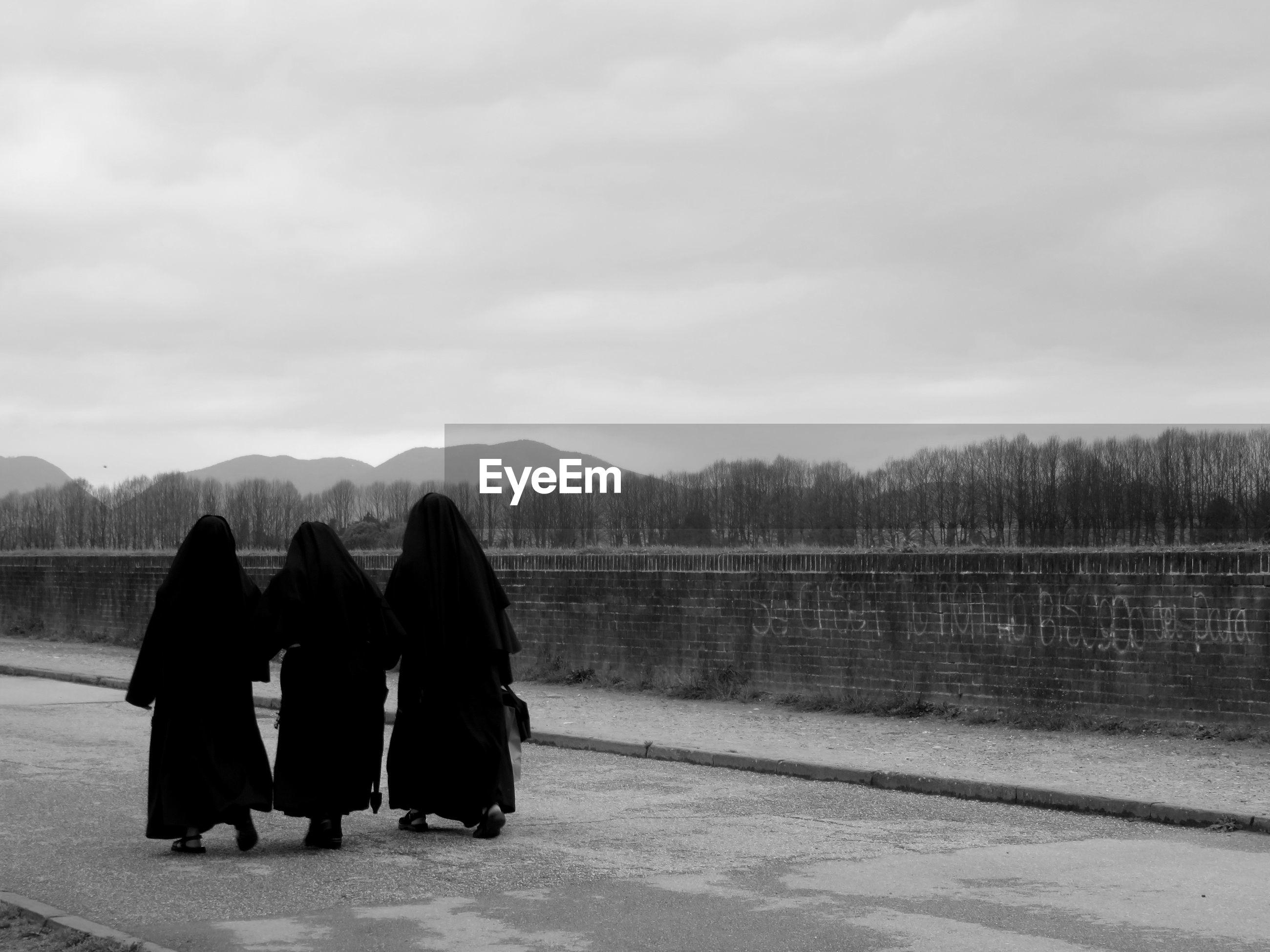 Rear view of women in burka walking on street