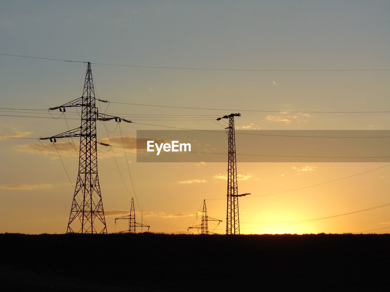 Low angle view of silhouette electricity pylons against the sky