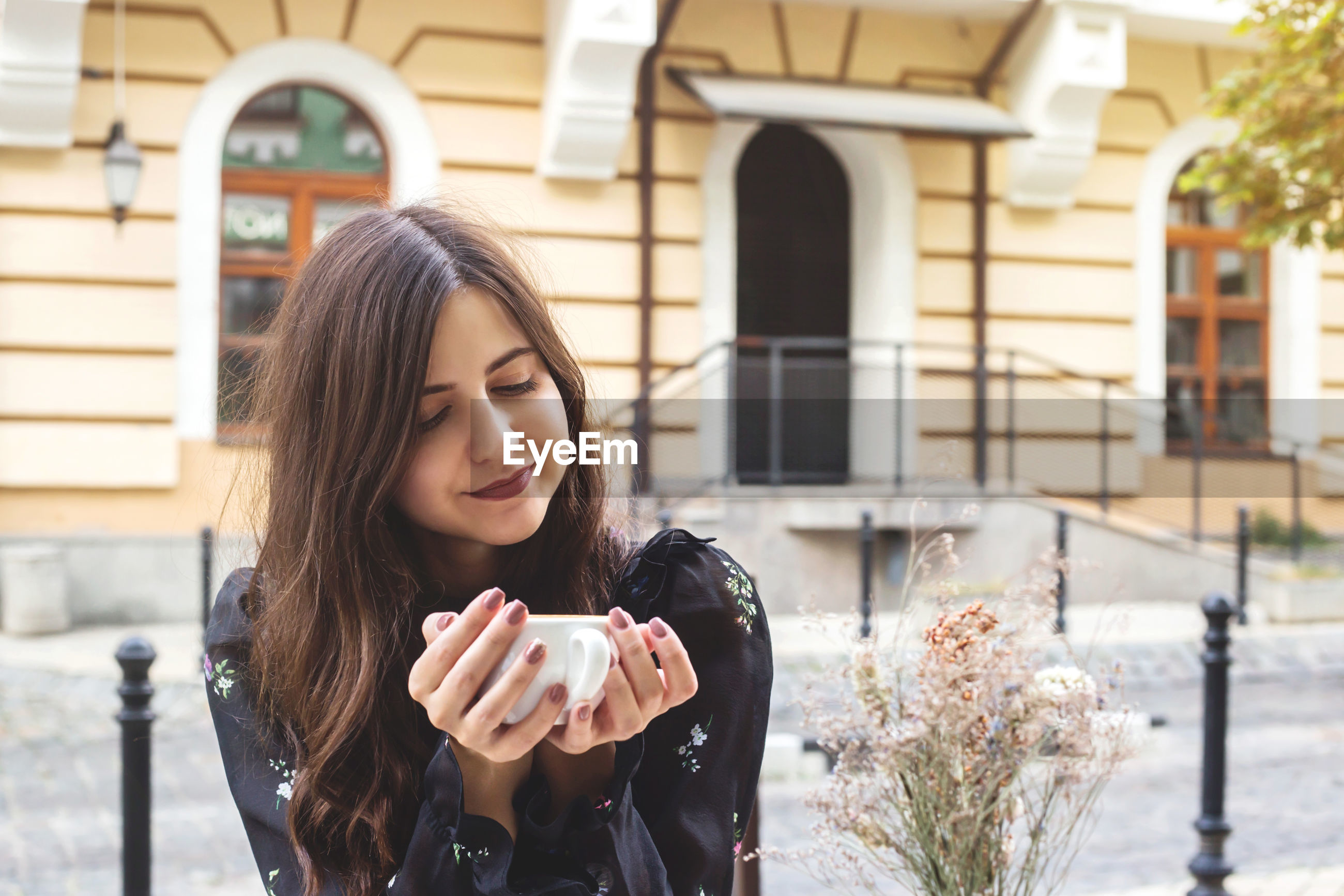Young woman having coffee while sitting at outdoor cafe in city