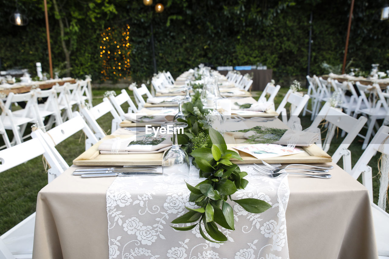 Chairs And Tables Arranged At Lawn During Ceremony