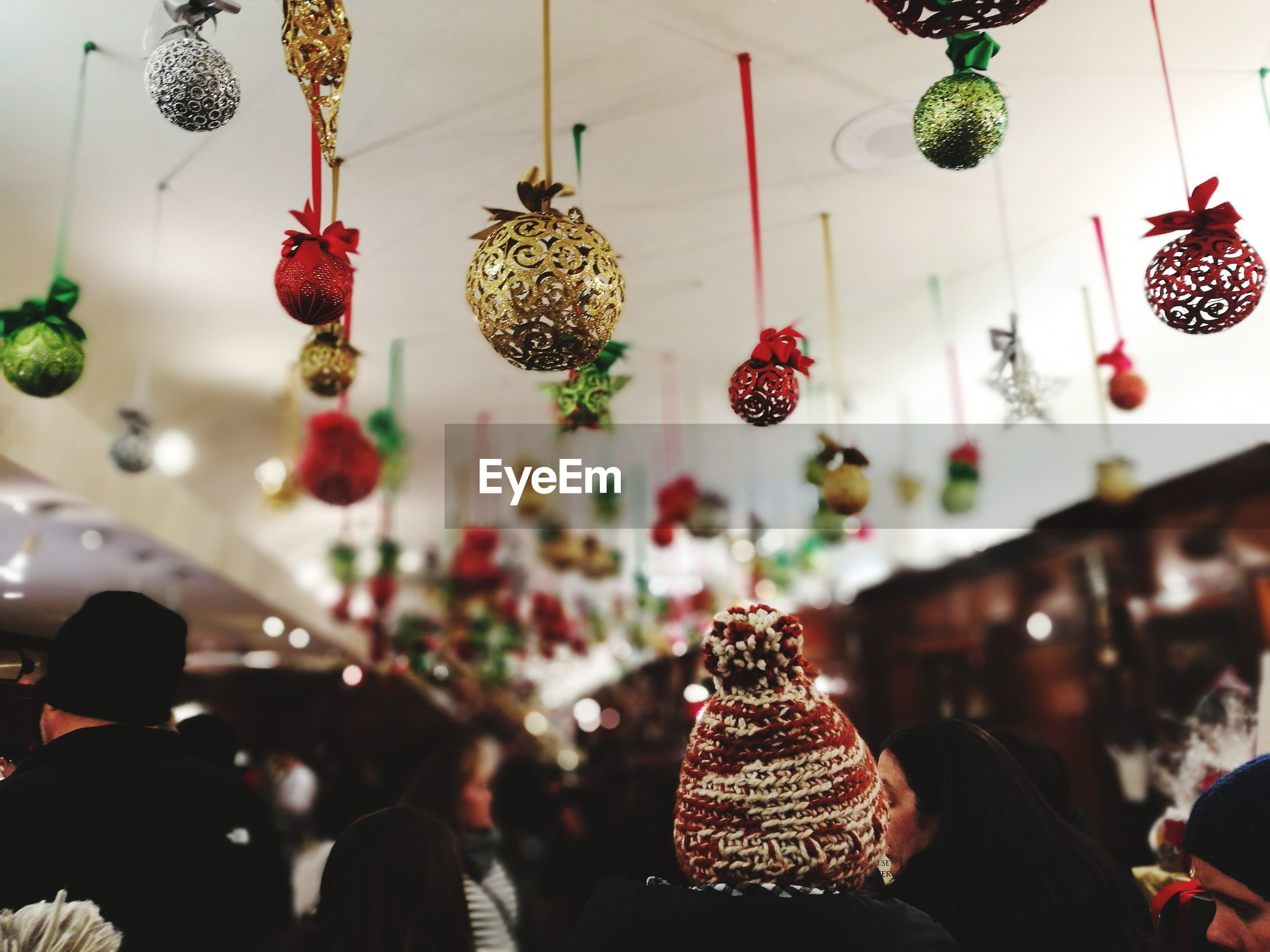Close-up of people with christmas decorations hanging in store