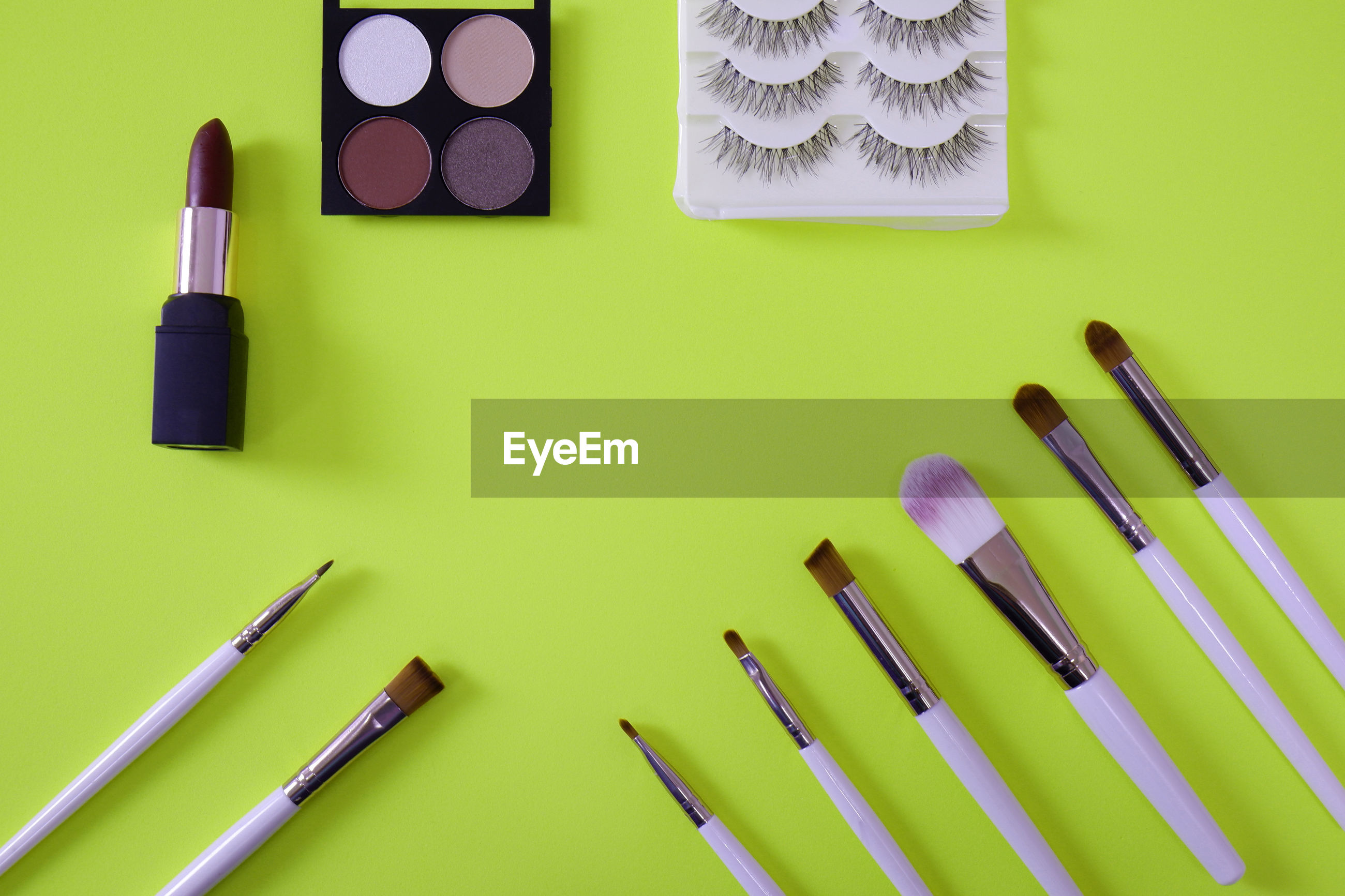 High angle view of make-up products on green background