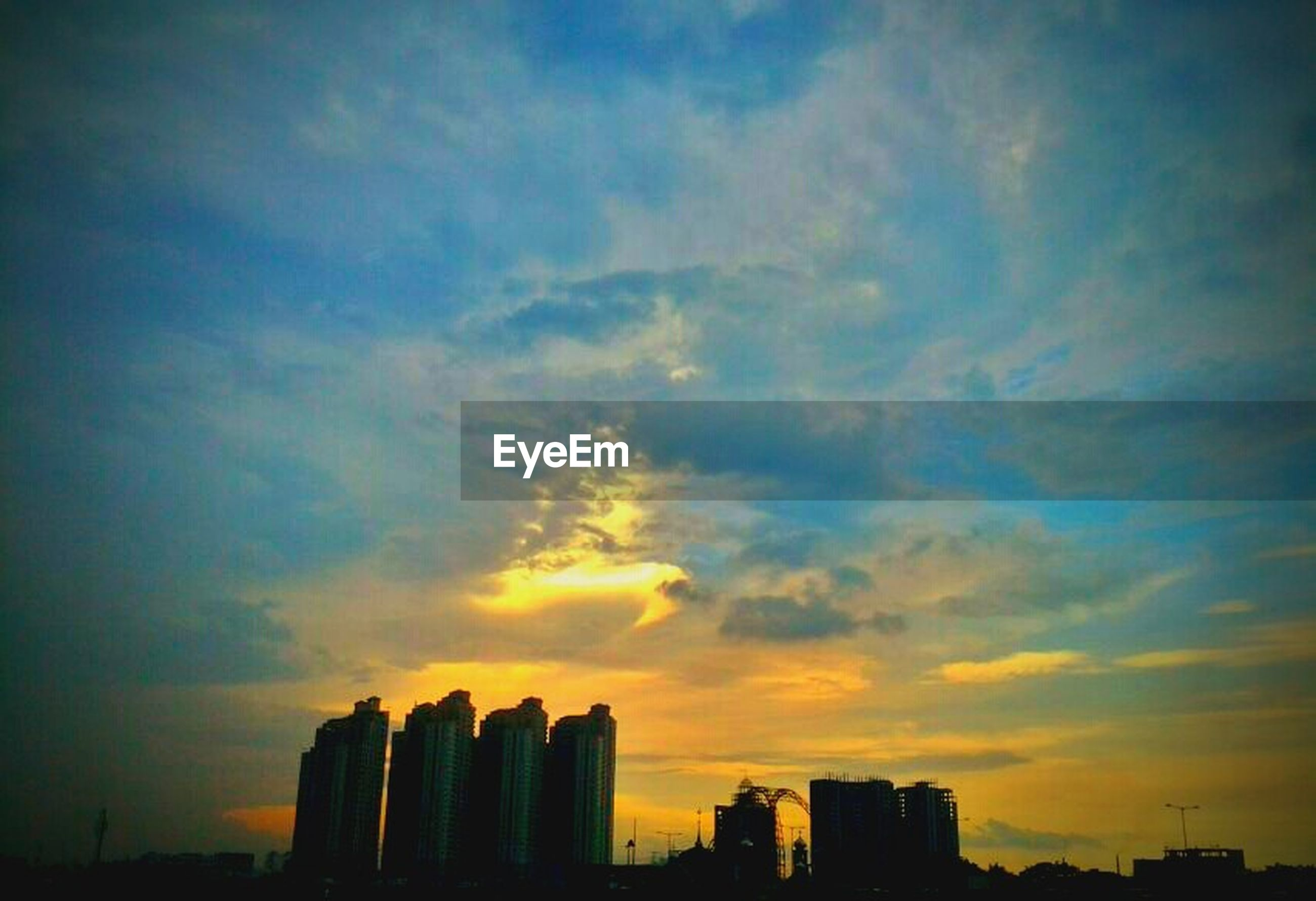 sunset, building exterior, silhouette, architecture, sky, built structure, city, cloud - sky, orange color, low angle view, cloud, beauty in nature, scenics, skyscraper, building, outdoors, nature, cityscape, no people, dramatic sky