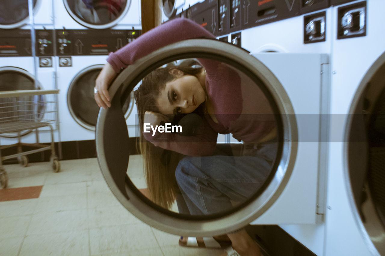 Portrait of woman looking through laundromat door