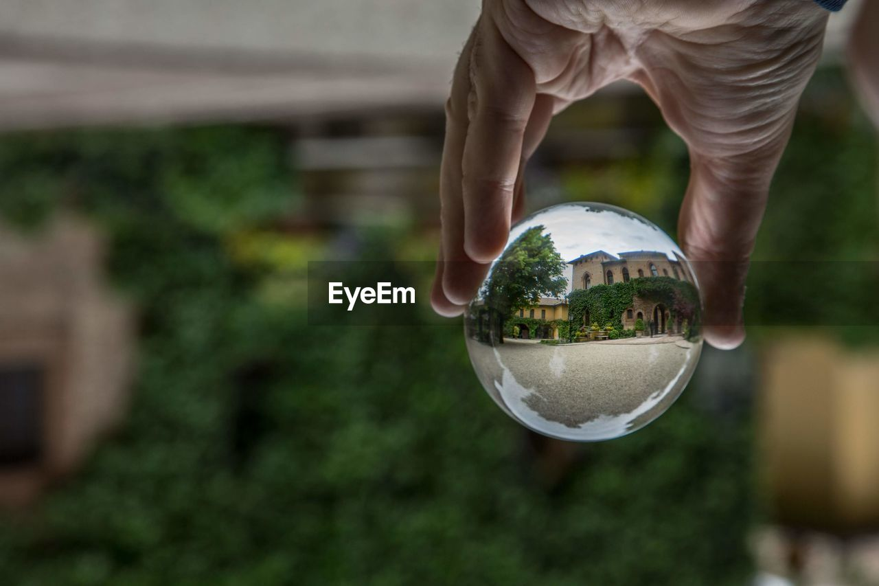 Cropped hand of person holding crystal ball in city