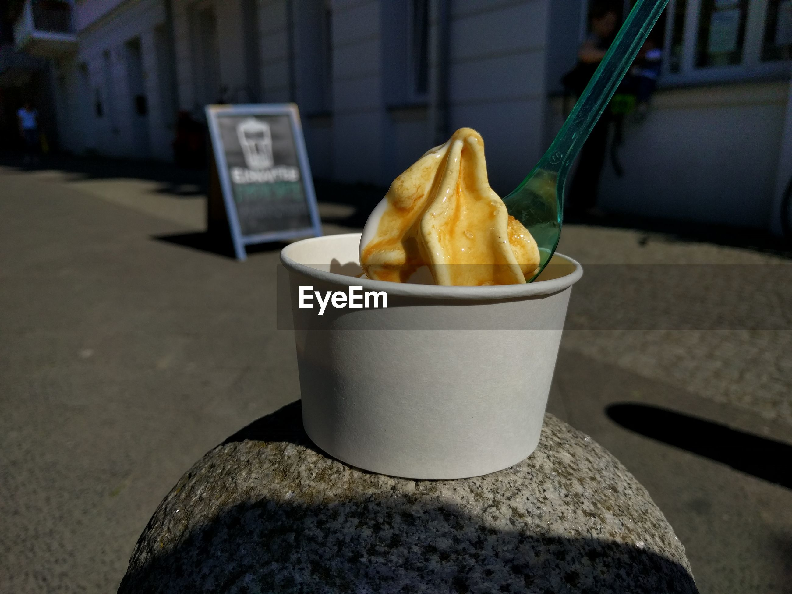 Close-up of ice cream cup on stone