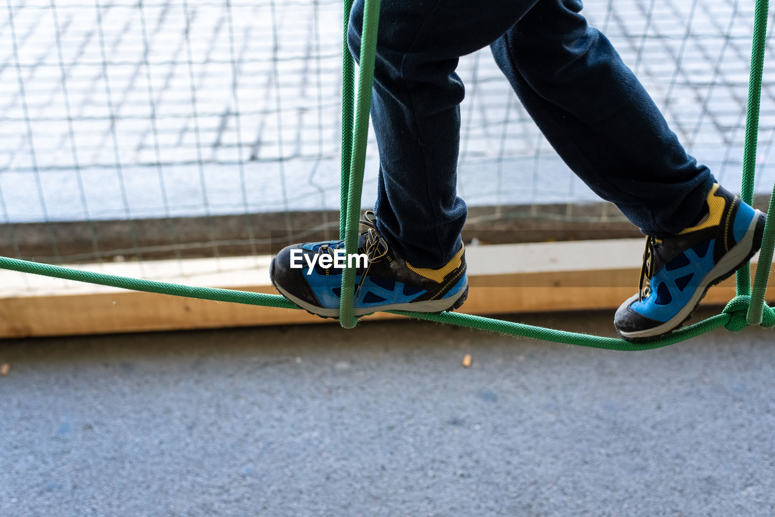 Low section of man walking on rope