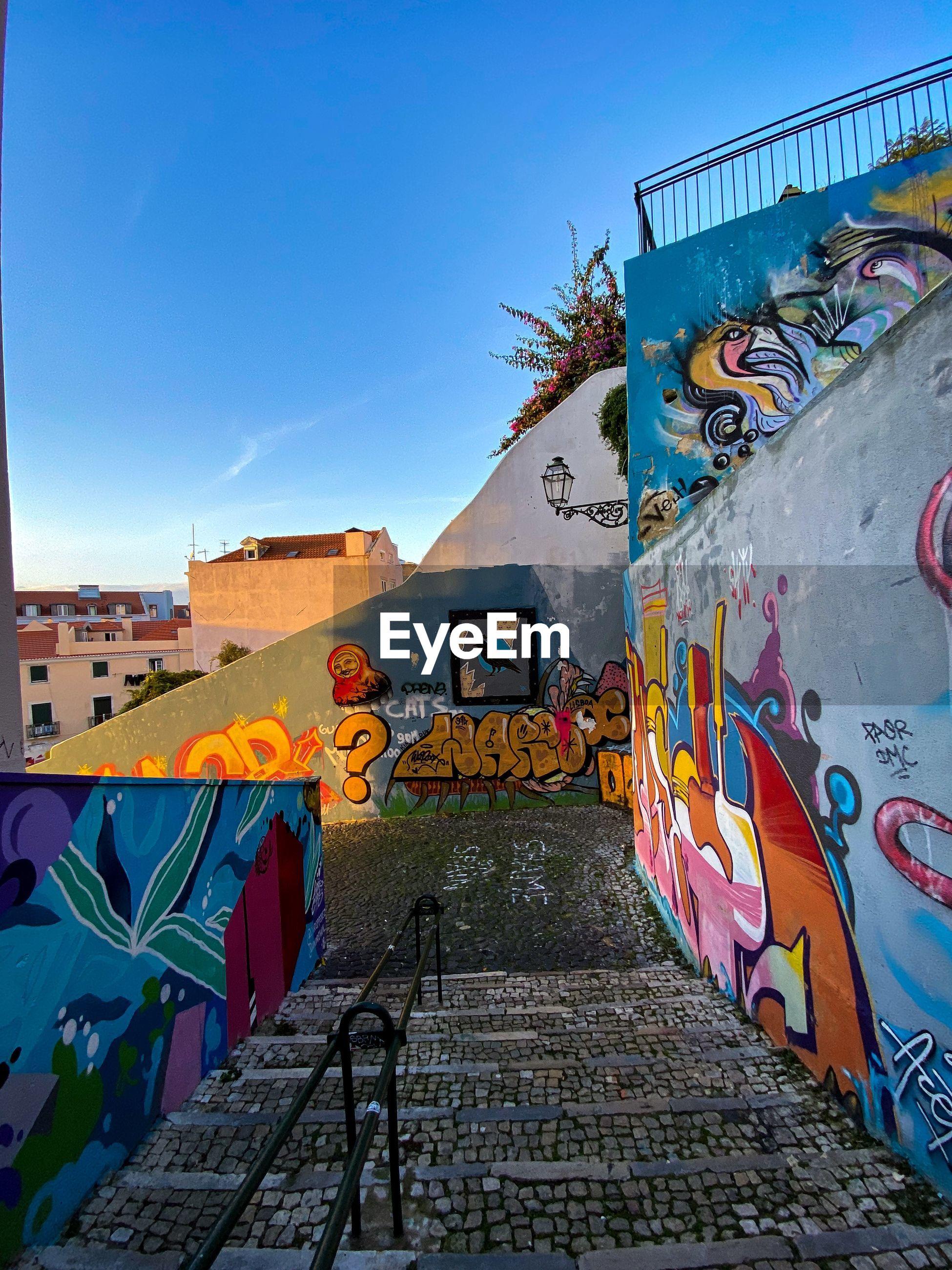 GRAFFITI ON BUILDING WALL AGAINST SKY