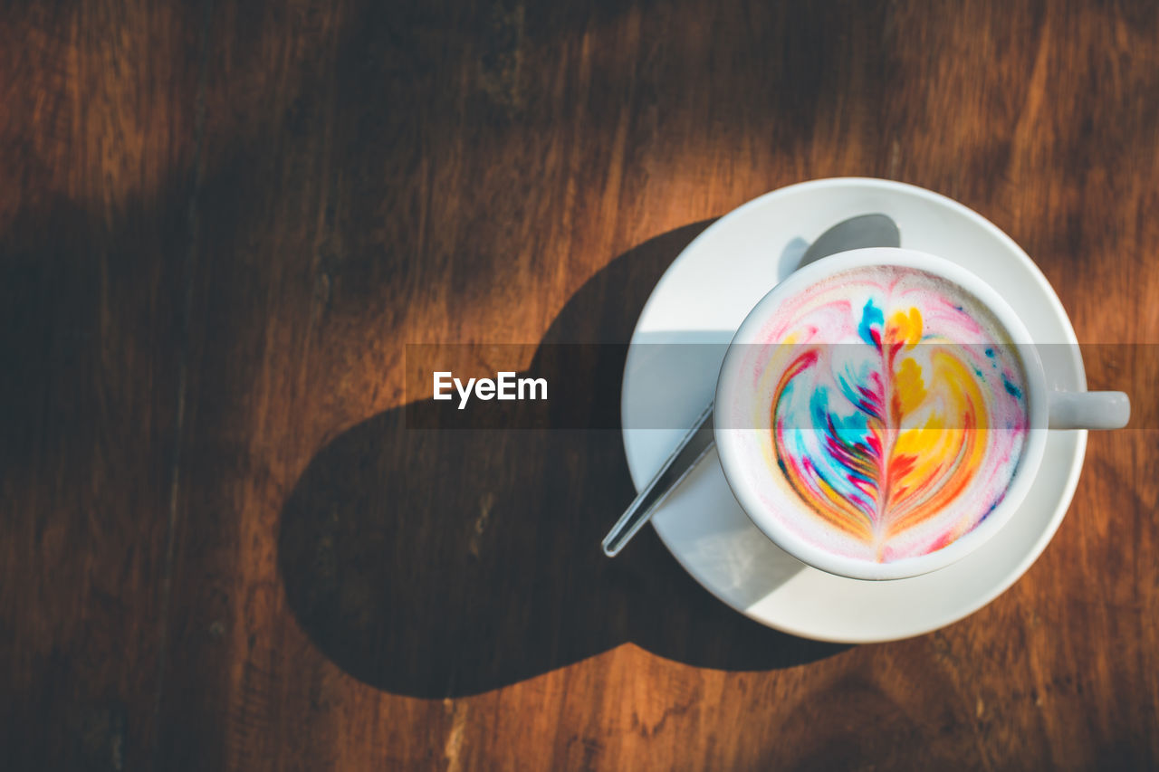High angle view of colorful coffee on wooden table
