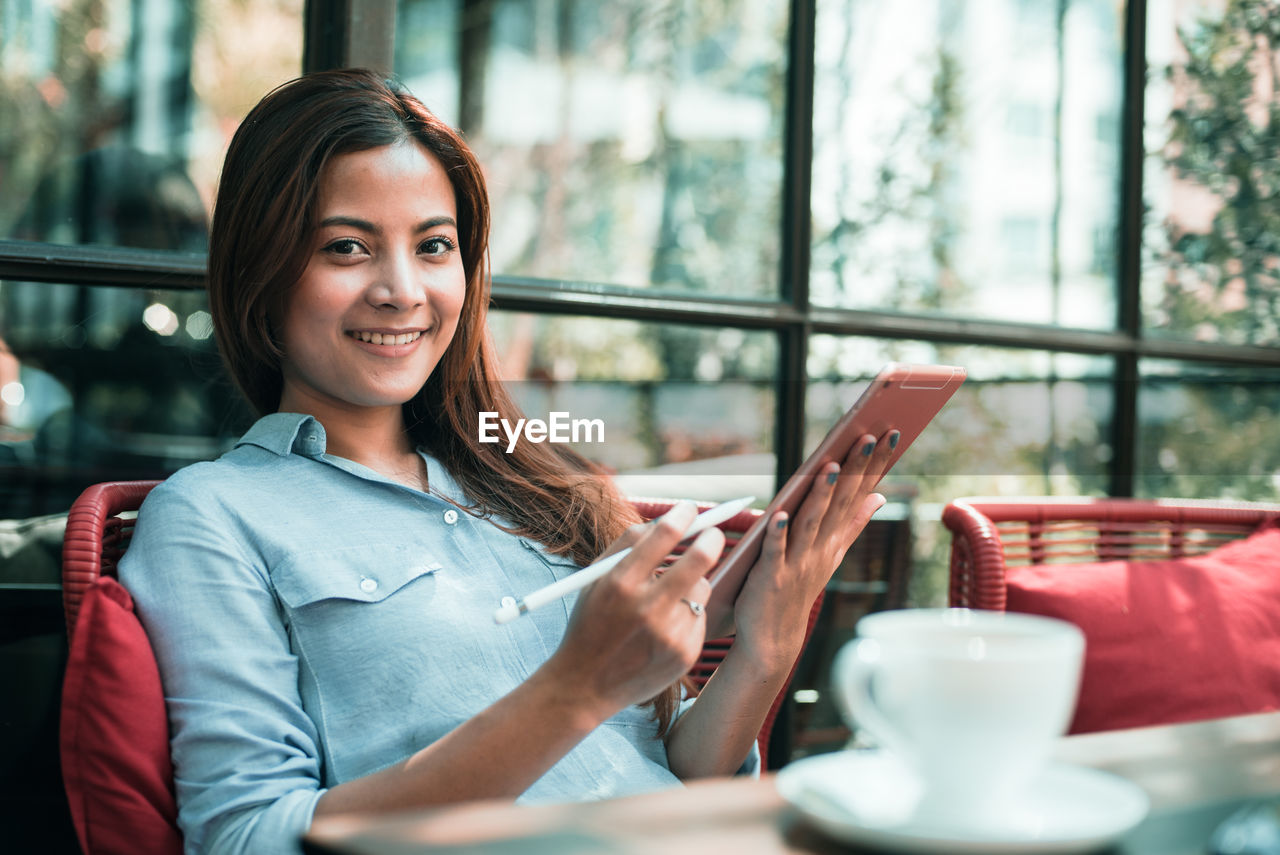 Young woman using digital table while sitting in cafe
