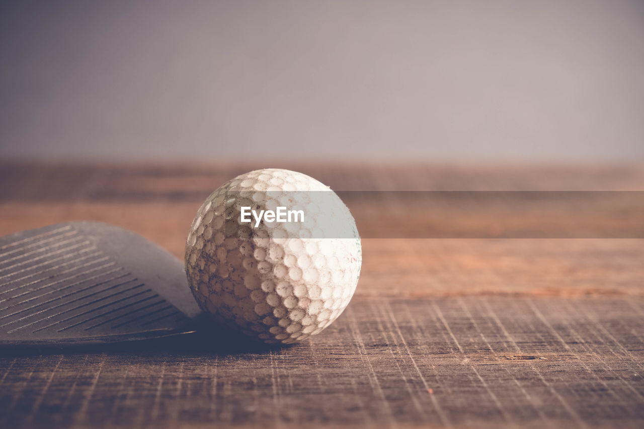 table, ball, close-up, still life, sphere, no people, selective focus, wood - material, focus on foreground, sport, golf, golf ball, indoors, day, leisure activity, pattern, two objects, nature, sunset
