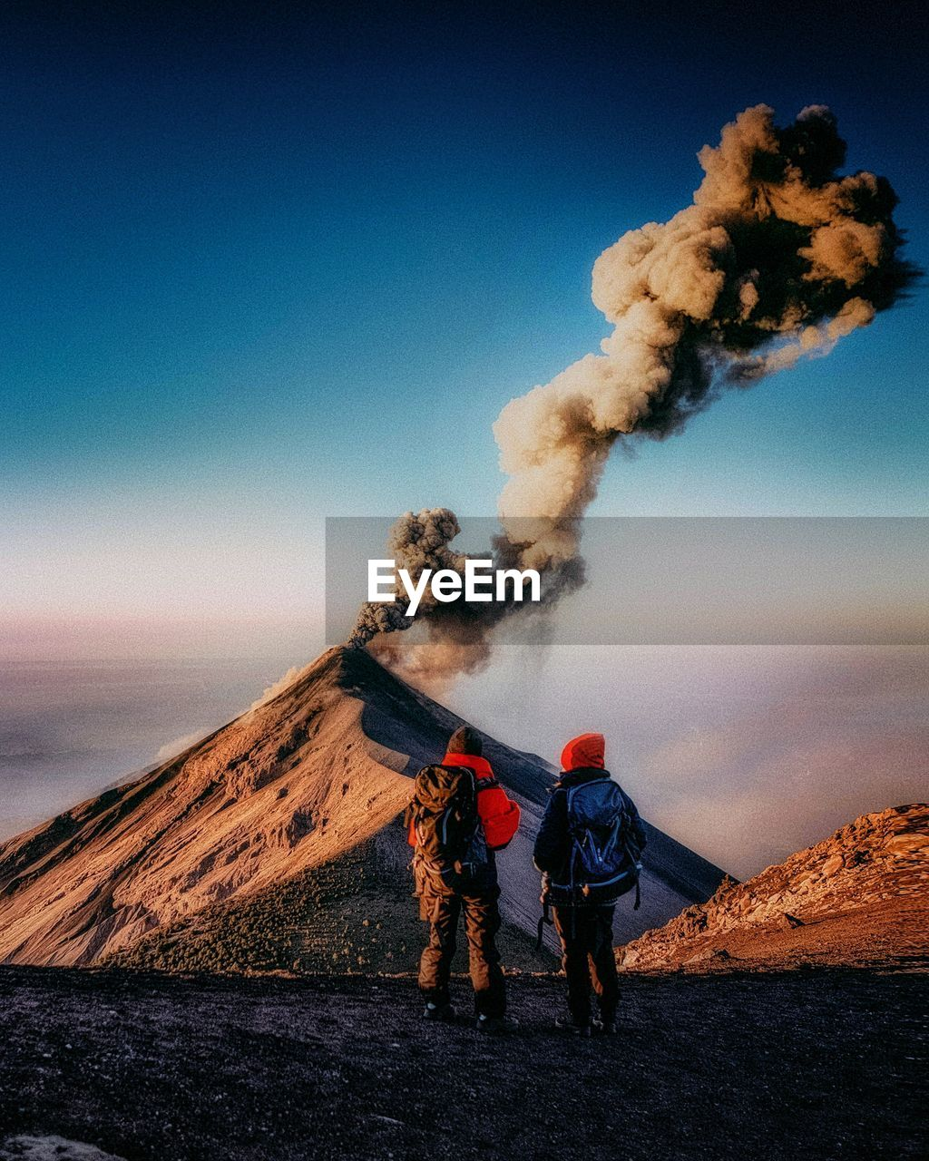 smoke - physical structure, sky, environment, mountain, two people, nature, landscape, men, beauty in nature, real people, day, heat - temperature, volcano, clear sky, non-urban scene, geology, people, land, scenics - nature, outdoors, volcanic crater, pollution, power in nature