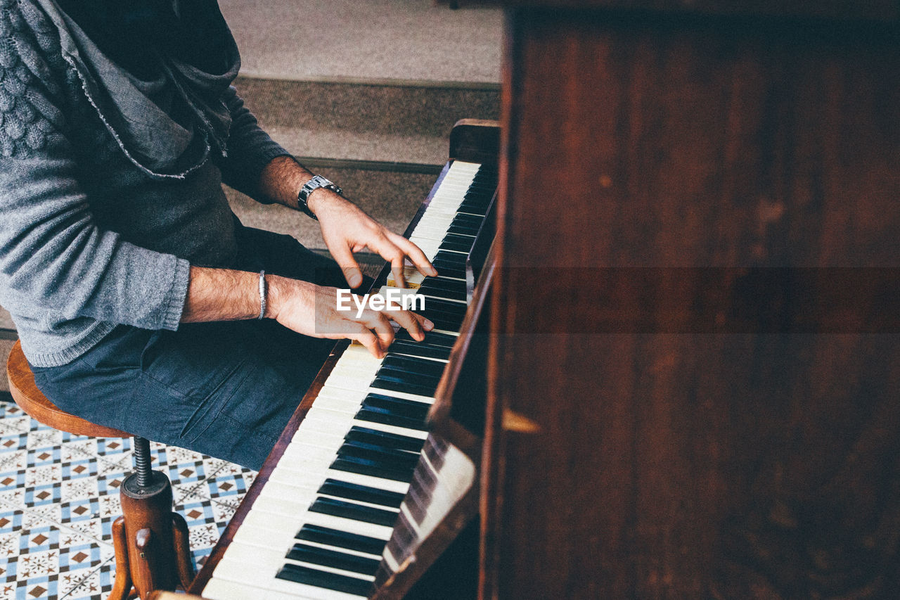 Midsection Of Man Playing Piano At Home