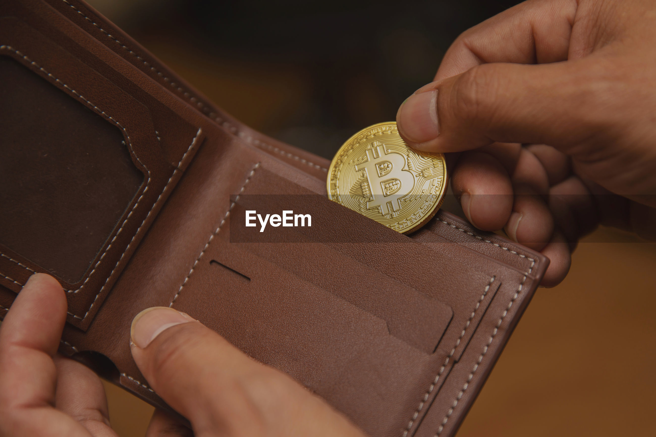 Cropped image of person inserting bitcoin in wallet at home