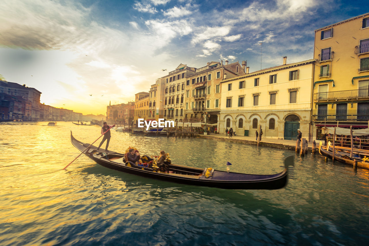 architecture, building exterior, built structure, canal, transportation, nautical vessel, mode of transport, sky, gondola, men, water, real people, city, gondolier, outdoors, gondola - traditional boat, day, people