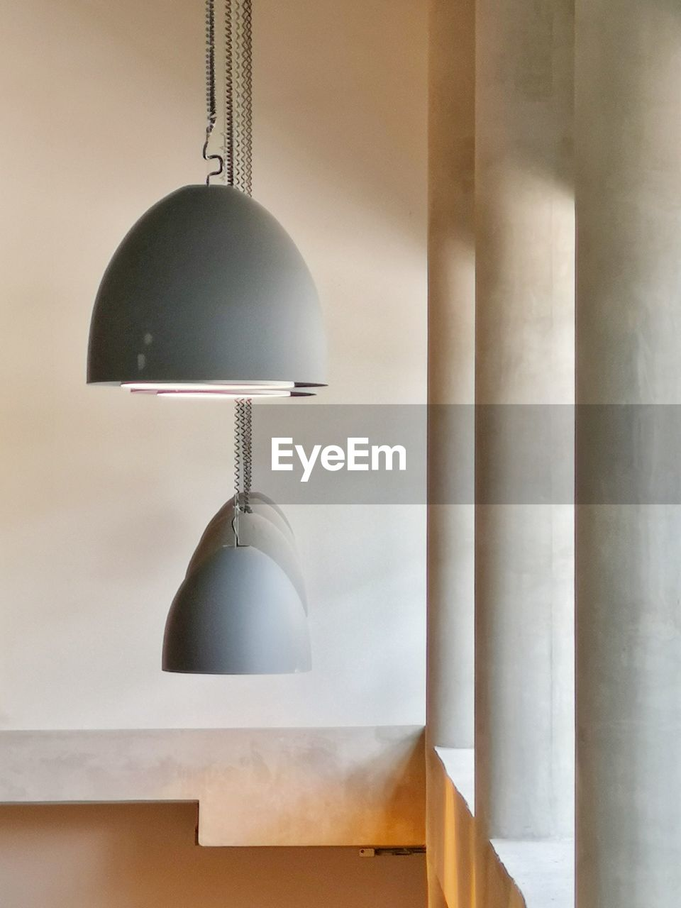 hanging, indoors, lighting equipment, pendant light, no people, electric lamp, wall - building feature, light, illuminated, electric light, decoration, white color, electricity, home interior, metal, close-up, lamp shade, ceiling, design, day, light fixture