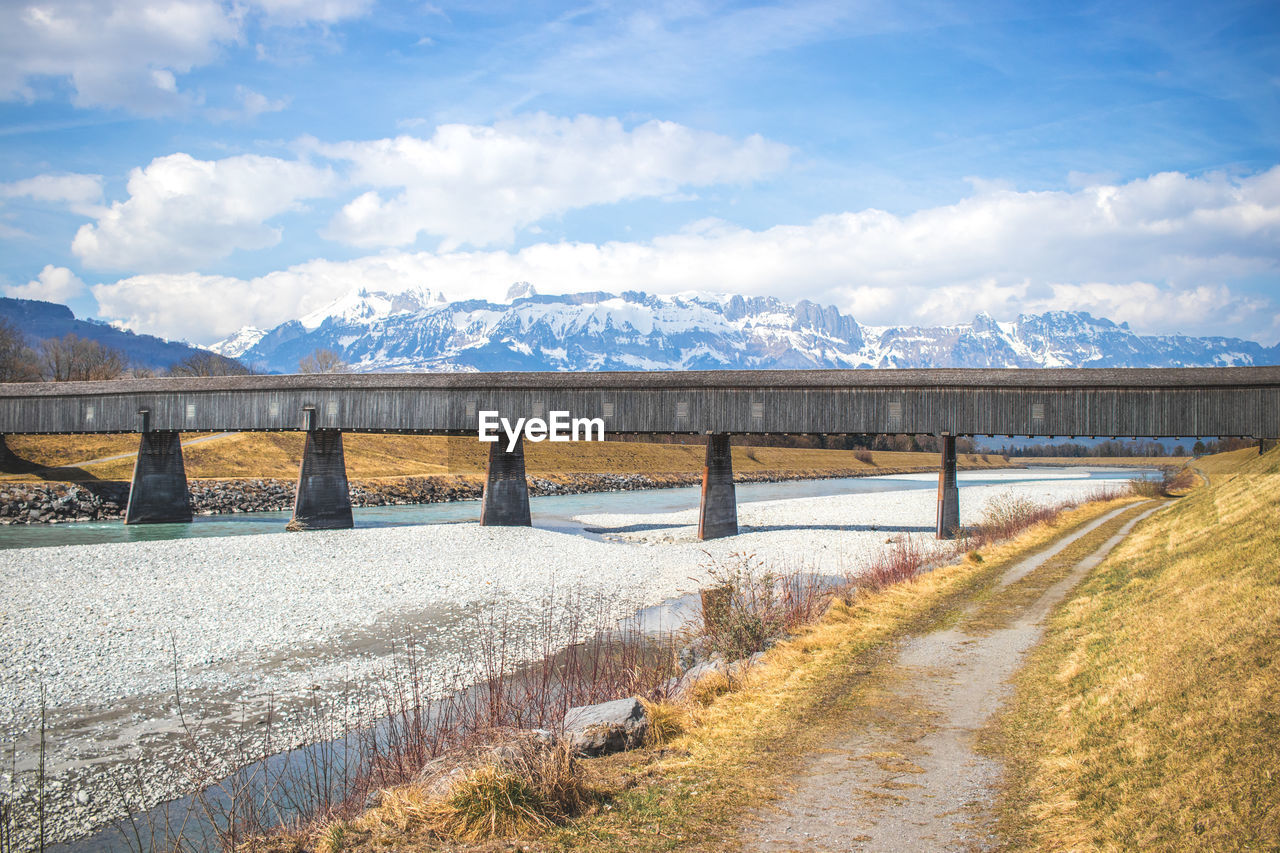 bridge - man made structure, connection, cloud - sky, sky, river, day, sunlight, outdoors, nature, architecture, water, built structure, bridge, scenics, no people, beauty in nature, landscape, grass, growth