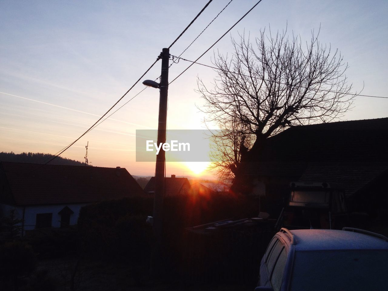 sunset, building exterior, car, built structure, cable, house, architecture, transportation, no people, silhouette, sky, mode of transport, outdoors, land vehicle, sunlight, tree, bare tree, nature, electricity pylon, day