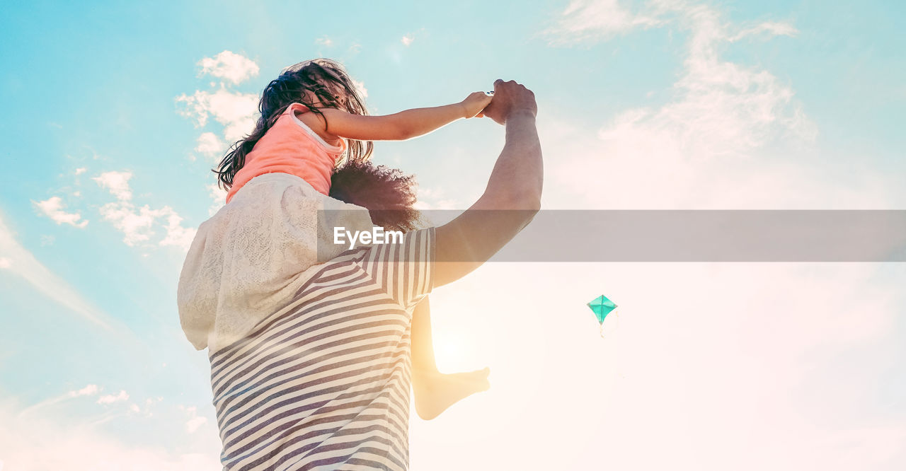 Father Carrying Daughter On Shoulders Against Sky