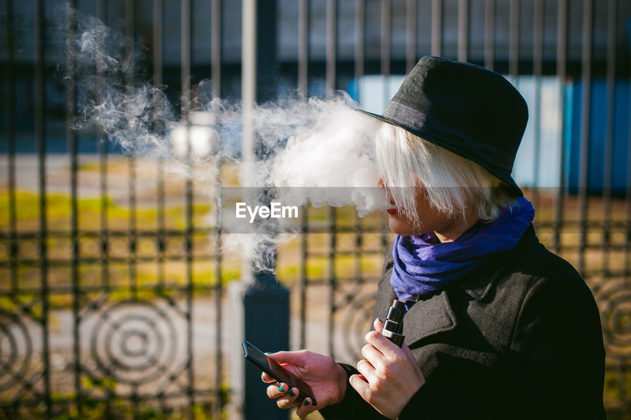 Side View Of Woman Using Mobile Phone While Smoking