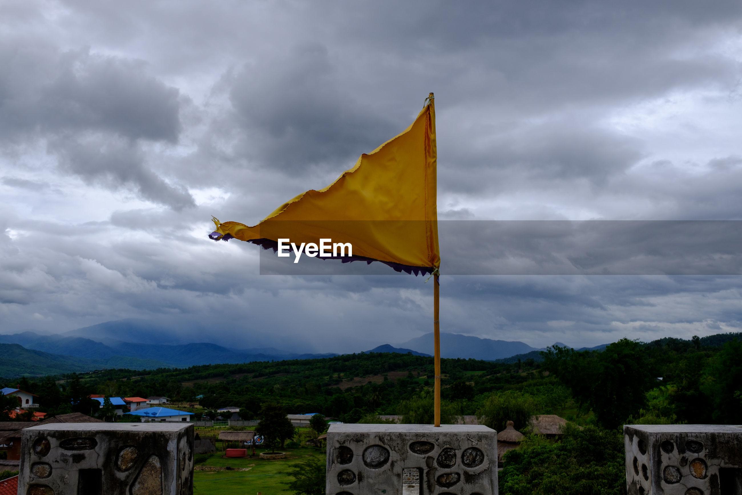 YELLOW FLAG AGAINST CLOUDY SKY