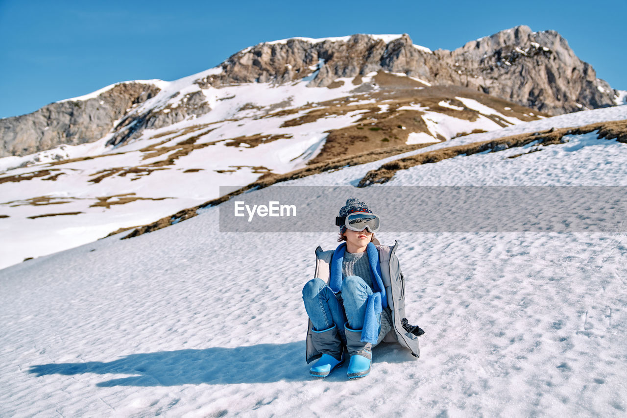 FULL LENGTH OF PERSON ON SNOWCAPPED MOUNTAINS