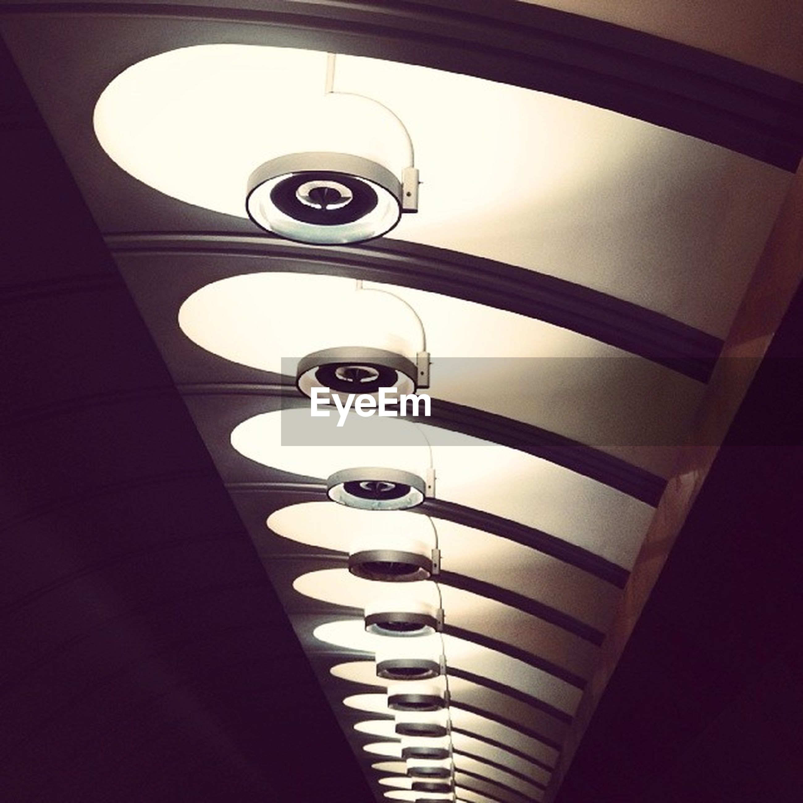 indoors, low angle view, ceiling, architecture, built structure, lighting equipment, illuminated, railing, circle, directly below, modern, pattern, electric light, staircase, geometric shape, no people, spiral, design, building, steps and staircases