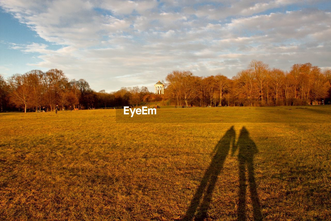Shadow Man And Woman On Grassy Field