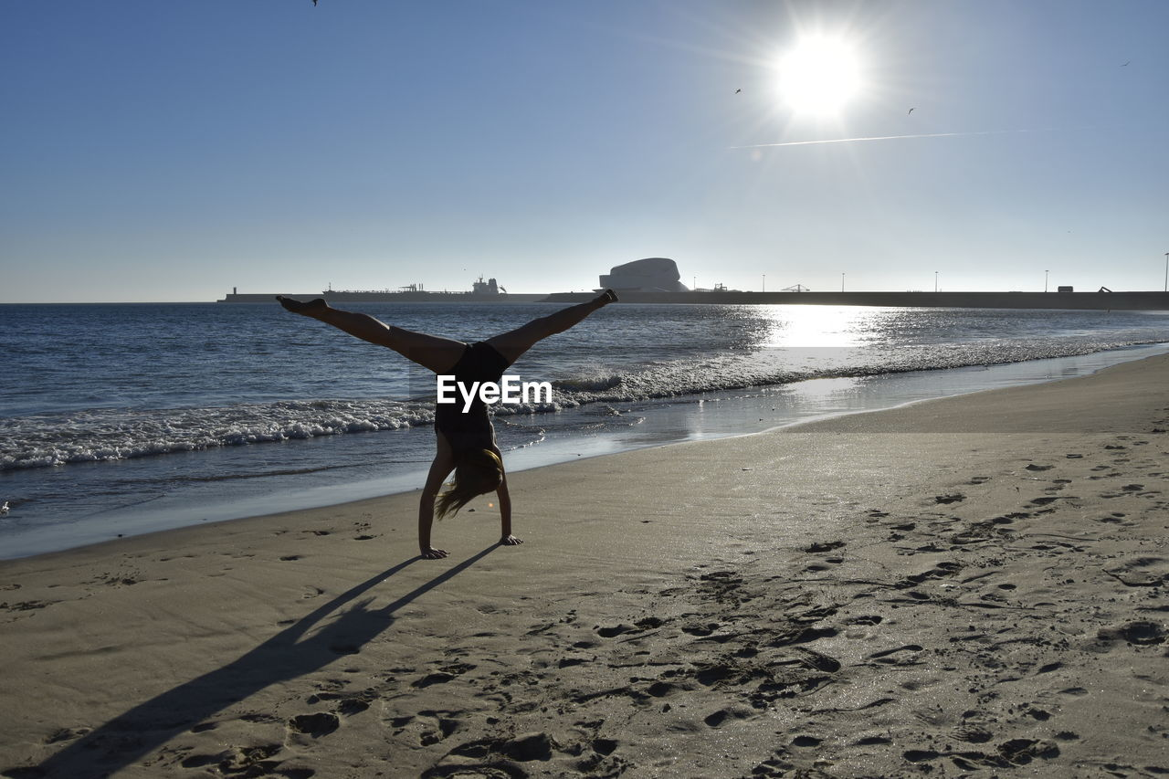 Rear view of woman practicing handstand at beach against sky
