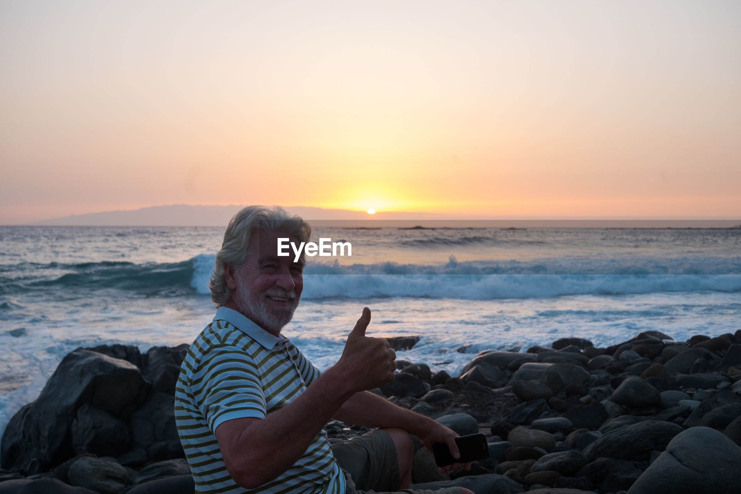 Portrait of smiling senior man showing thumbs up while sitting on rock at beach during sunset
