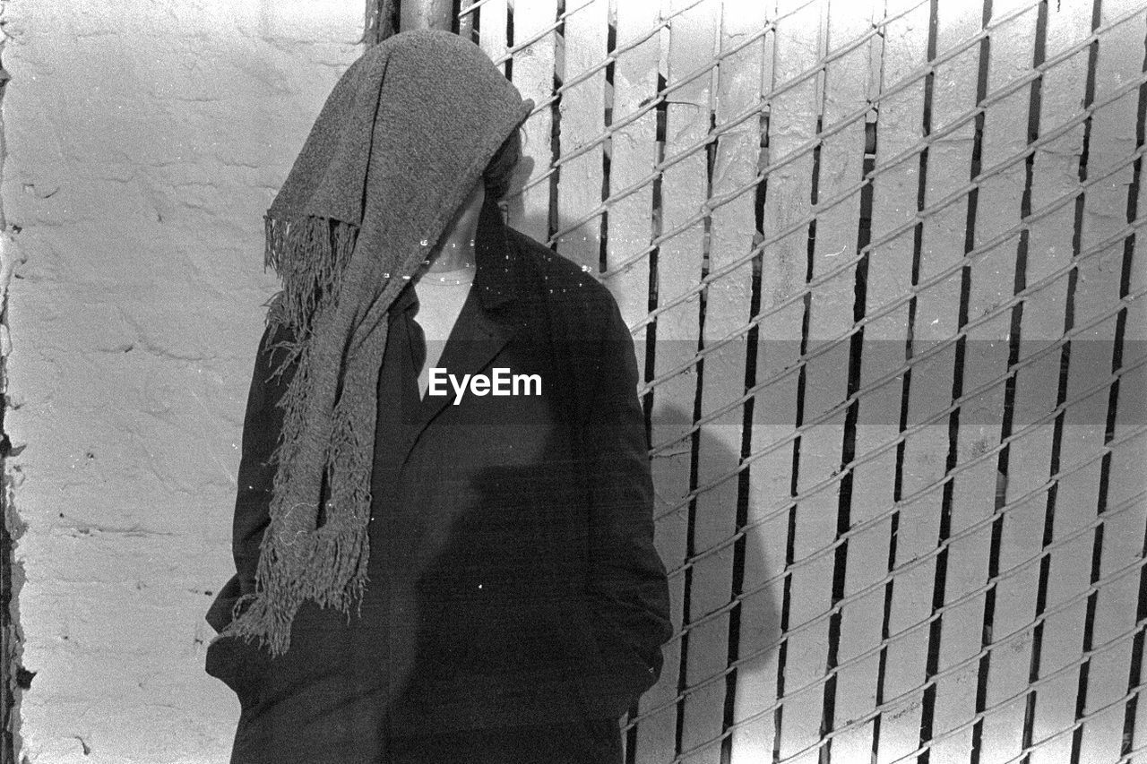 Man face covered with scarf standing against wall