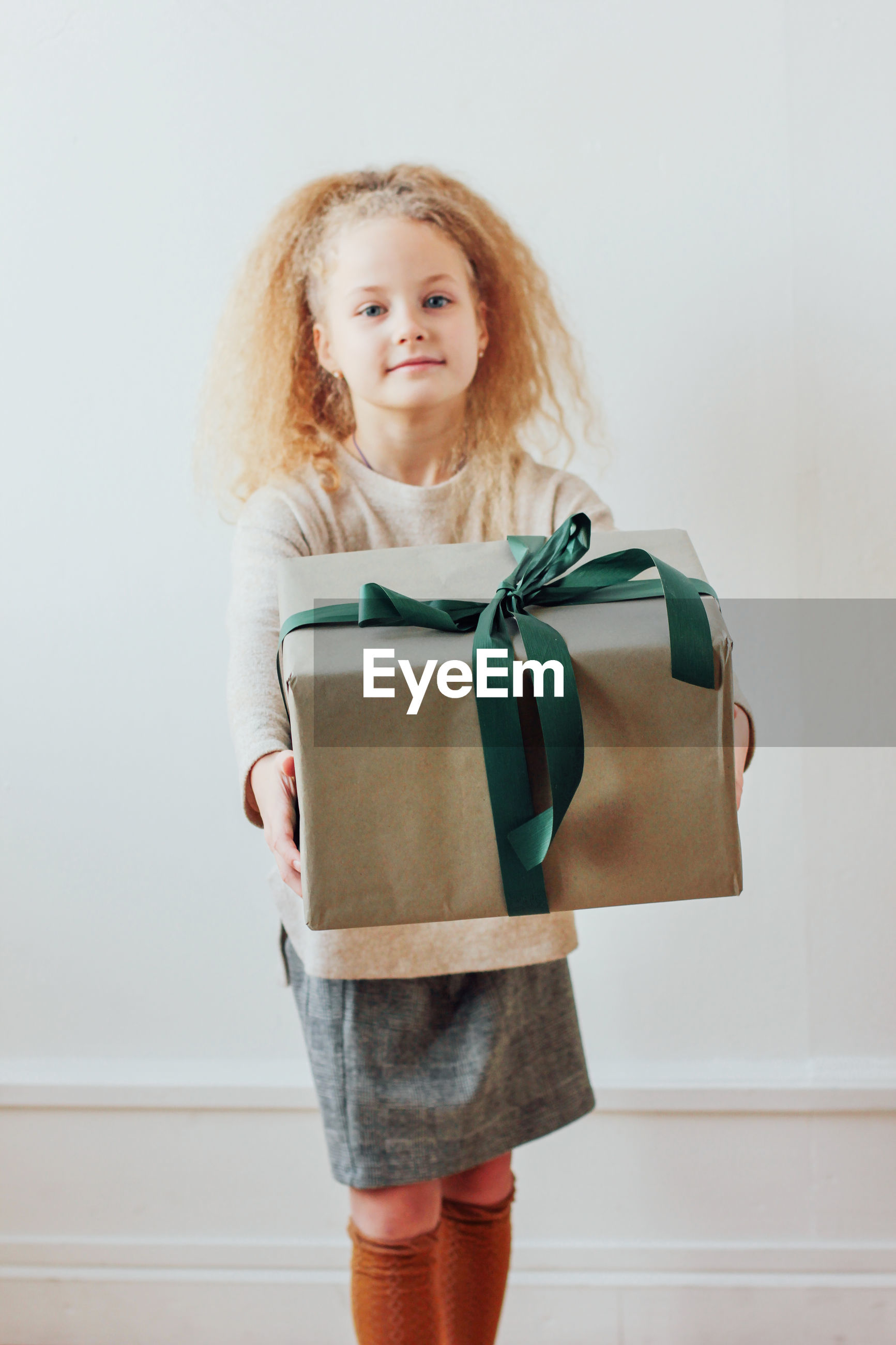 Portrait of girl holding christmas present against wall