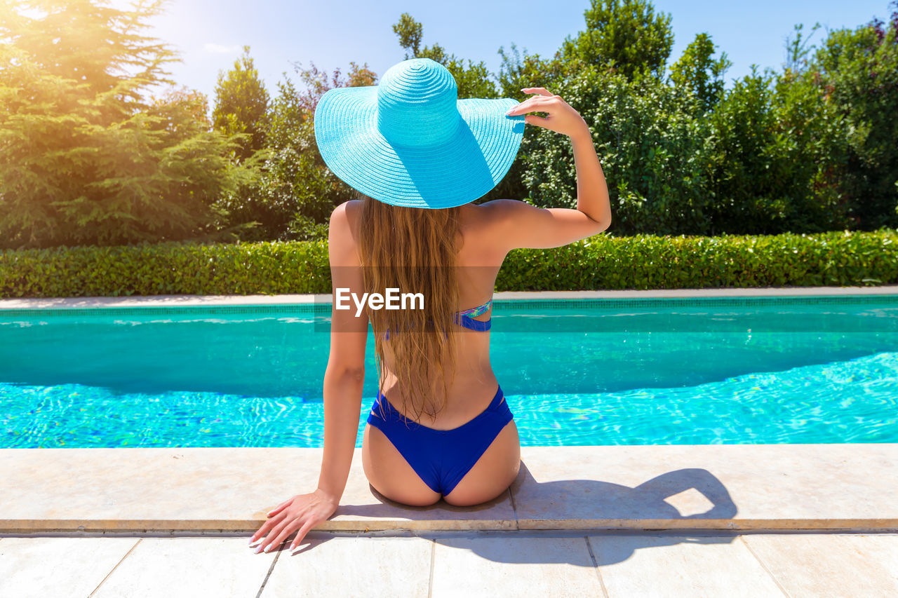 Rear View Of Woman Wearing Hat While Sitting On Poolside