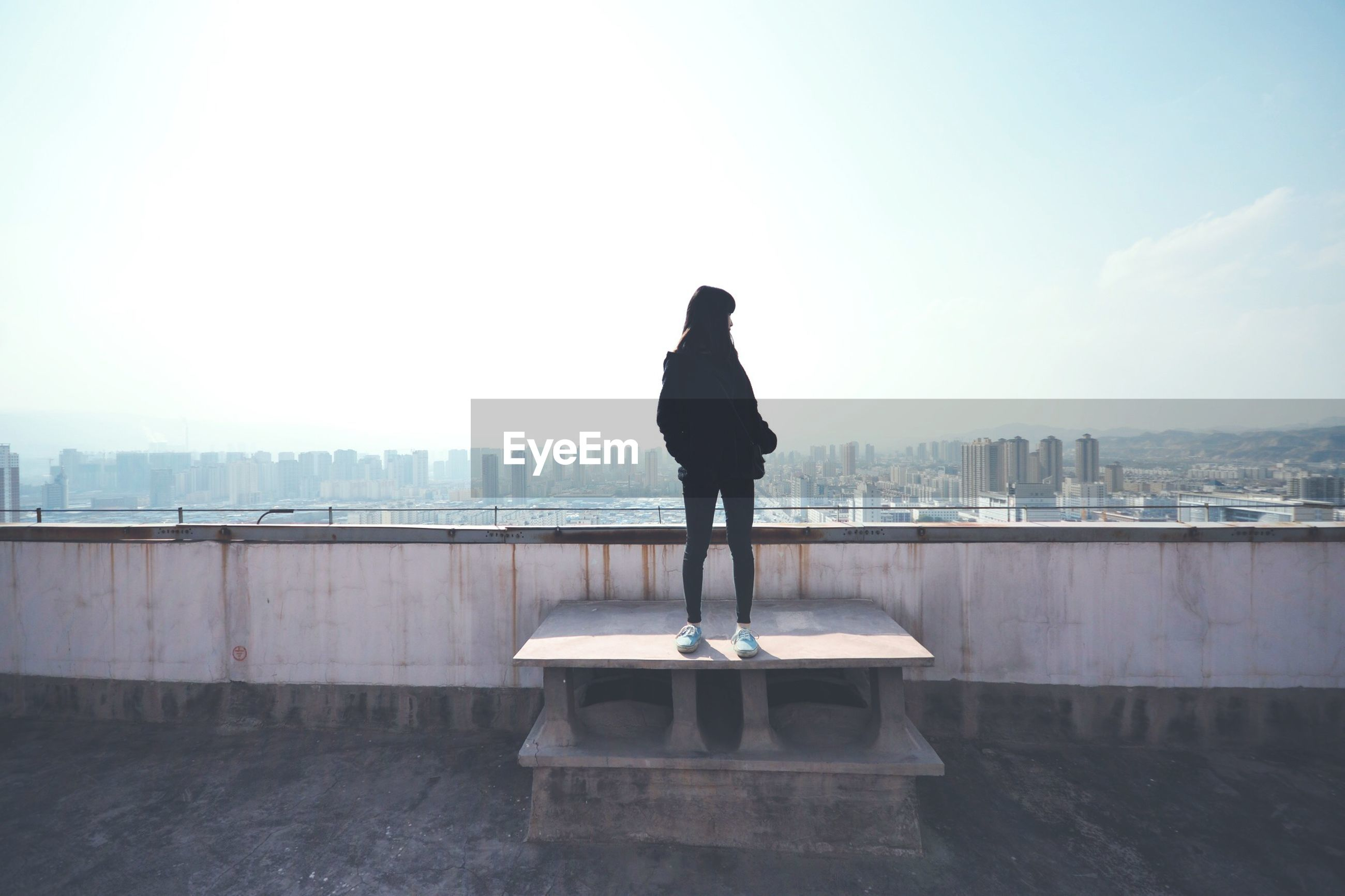 Woman standing by railing against sky in city