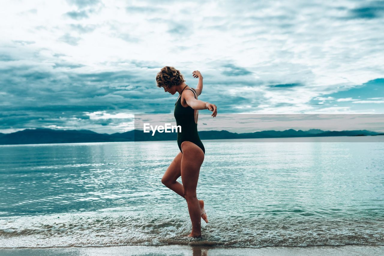 Side View Of Young Woman In Swimwear Walking At Lakeshore Against Cloudy Sky