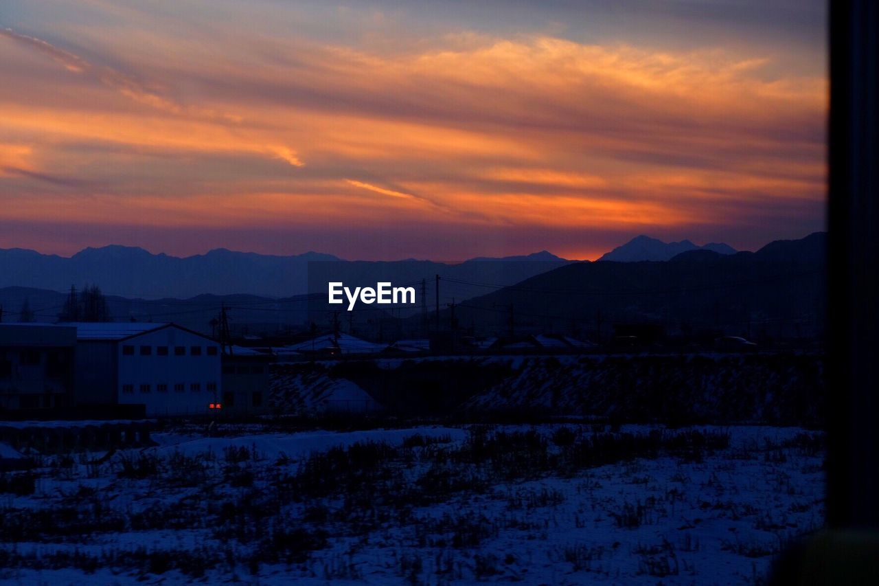mountain, sunset, sky, nature, no people, winter, snow, beauty in nature, scenics, mountain range, cold temperature, outdoors, tranquil scene, architecture, cloud - sky, silhouette, built structure, building exterior, landscape, day