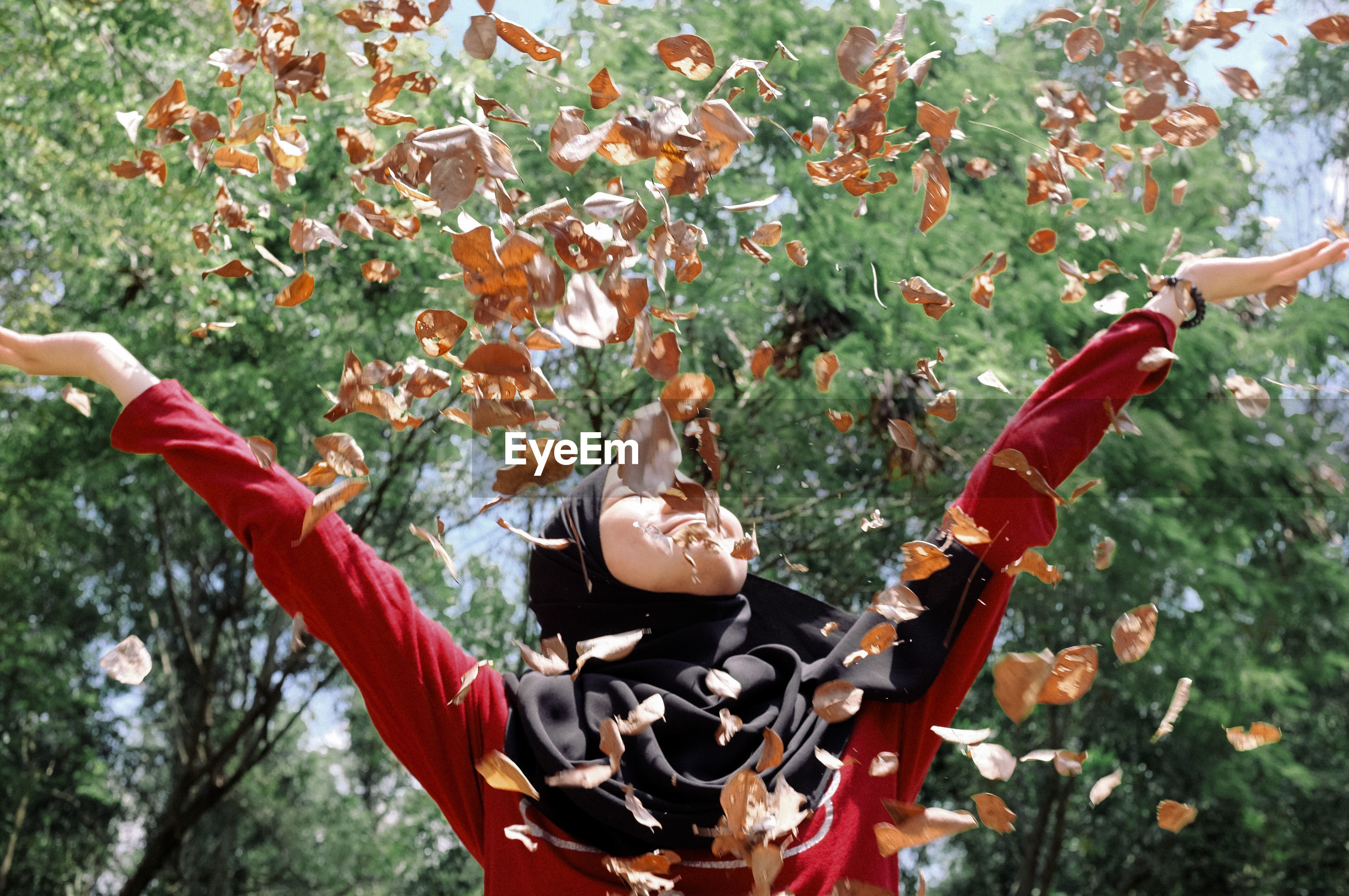 A girl in hijab throwing dried leaves up in the air